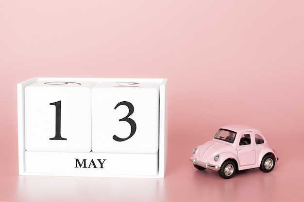 Close-up wooden cube 13th of may. day 13 of may month, calendar on a pink background with retro car. Premium Photo