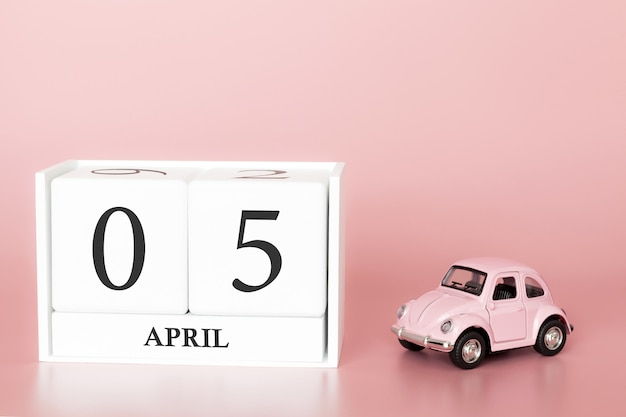 Close-up wooden cube 5th of april. day 5 of april month, calendar on a pink with retro car. Premium Photo