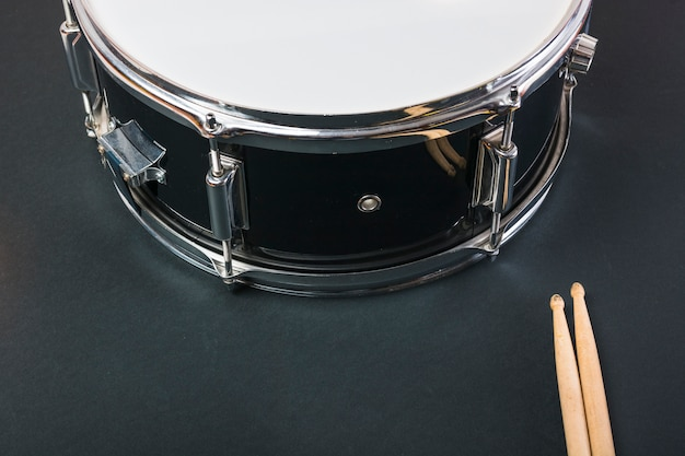 Close-up of wooden drumsticks and drum on black background Premium Photo