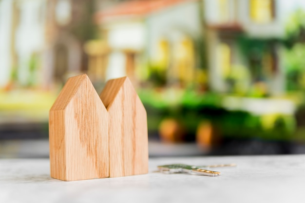 Close-up of wooden house structure with keys on surface against blur background Free Photo