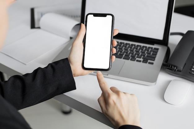 Крупным планом работник держит мобильный телефон Бесплатные Фотографии