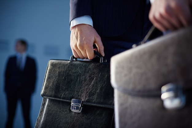 Close-up of workers with briefcases Free Photo