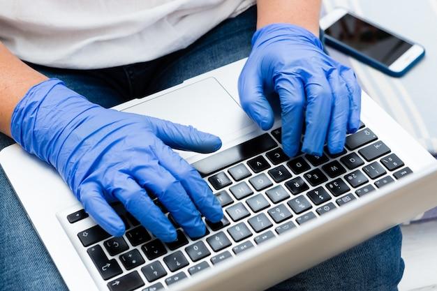 Закройте вверх работая домашняя женщина печатая на компьтер-книжке с хирургическими перчатками Premium Фотографии