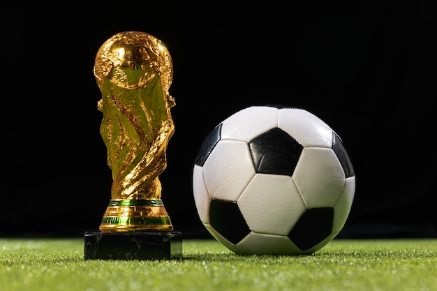 Close-up world cup trophy with soccer ball Free Photo