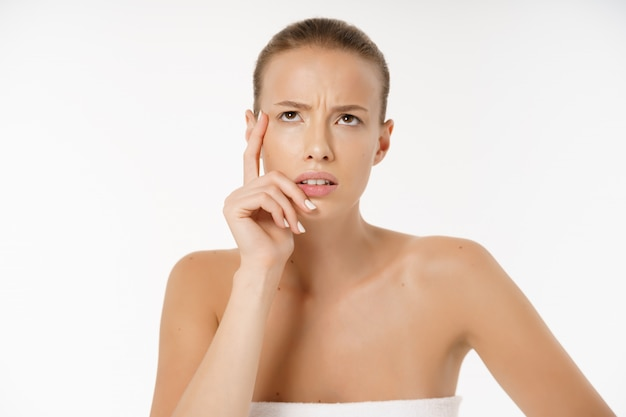 Close-up of worried woman looking at pimple on face Premium Photo