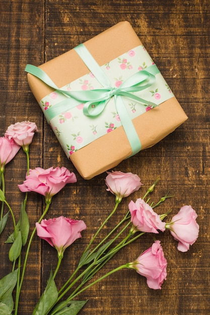 Close-up of wrapped parcel and pink fresh flower on table Free Photo