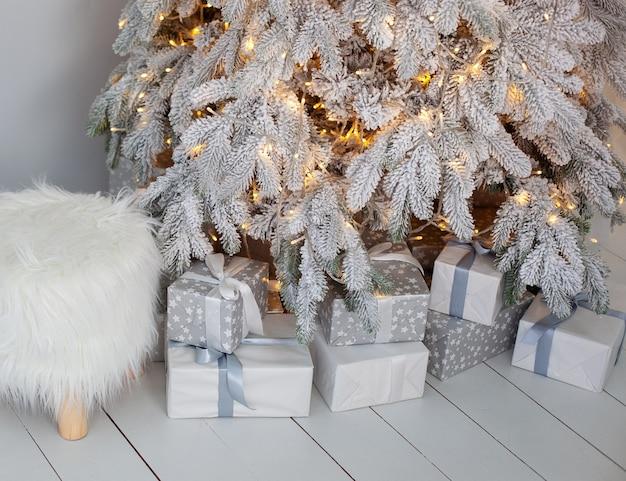 リビングルームのクリスマス雪の木の近くの床にクローズアップのクリスマスプレゼント。 Premium写真