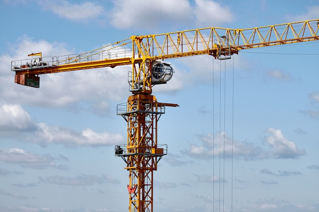 Close-up of a yellow construction crane on a blue sky background, selective focus Premium Photo