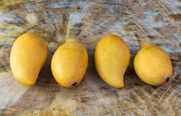 Close up yellow fresh mangos on real wood table. mango tropical fruit. 4 mango. Premium Photo