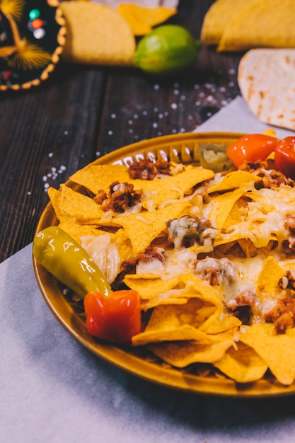 Close-up of yellow mexican nachos in plate on butter paper Free Photo