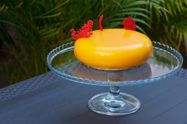 Close-up of yellow modern round-shaped cake on glassy stand Free Photo