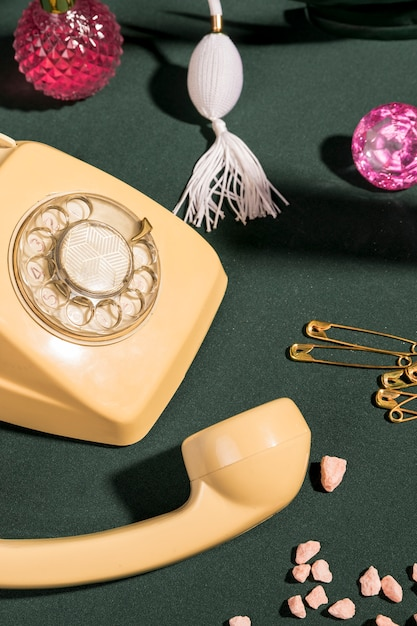 Close up yellow telephone next to girly items Free Photo