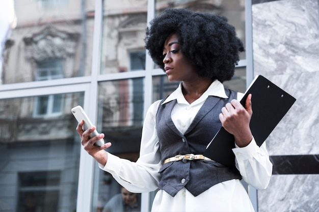 Close-up of a young african businesswoman holding clipboard using mobile phone Free Photo