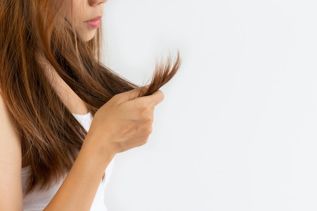 Close up of young asian girl looking at her damage hair on white wall with copy space Premium Photo