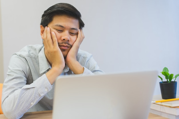Close up young asian man feeling bored and sleepy at desk , lifestyle concept Premium Photo
