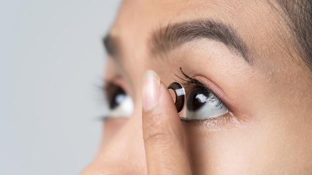 Close-up young asian woman wearing contact lens, macro shot. Premium Photo
