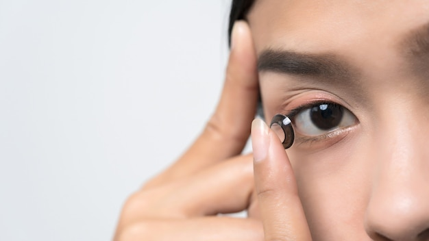 Close-up young asian woman wearing contact lens. Premium Photo