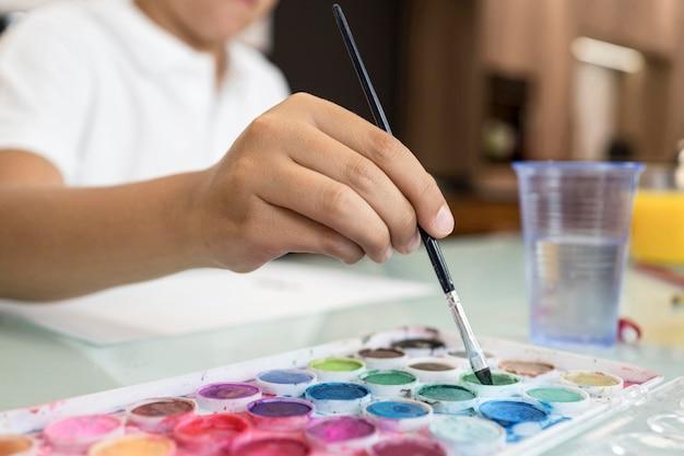 Giovane ragazzo del primo piano che dipinge a casa Foto Gratuite