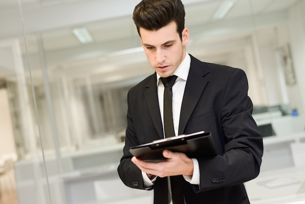 Close-up of young businessman reading a document Free Photo