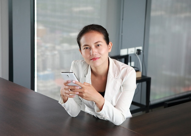 Close-up young businessman sitting at the chair on workplace in office using the smartphone Premium Photo