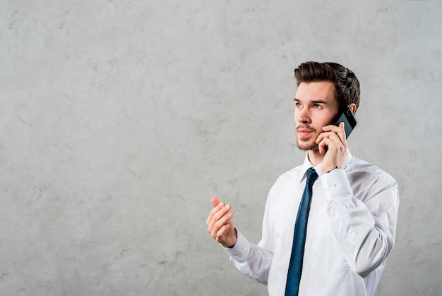 Close-up of a young businessman talking on smartphone looking away against grey concrete wall Free Photo