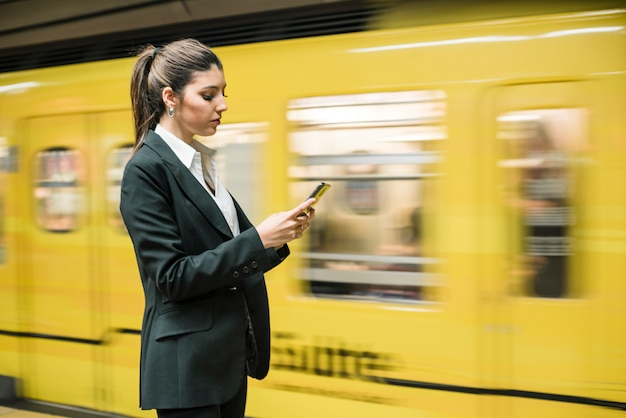 Close-up of a young businesswoman using mobile phone at the subway station Free Photo