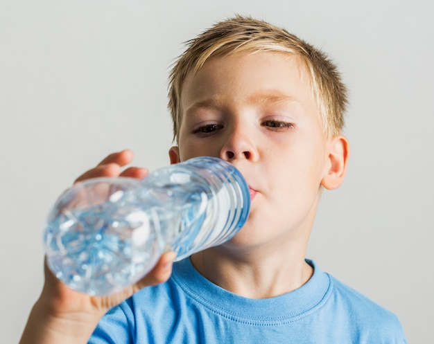 Close-up young child drinking water Free Photo