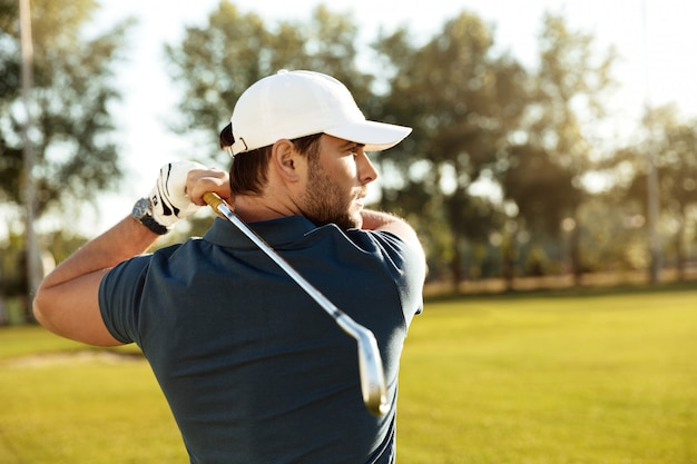 Close up of a young concentrated man shooting golf ball Free Photo