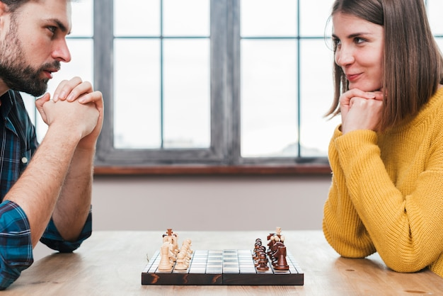 Close-up of young couple with their hand clasped looking at each other playing chess Free Photo