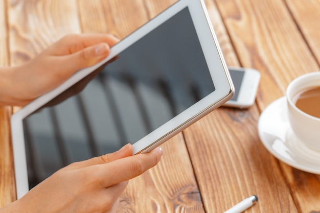 Close-up of young female hands holding digital tablet and drinking morning macchiato. Premium Photo
