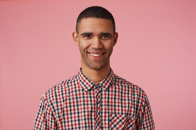 Primo piano di giovane ragazzo dalla pelle scura attraente felice in camicia a scacchi, guarda la telecamera con espressione positiva, ampiamente sorridente e si leva in piedi su sfondo rosa. Foto Gratuite