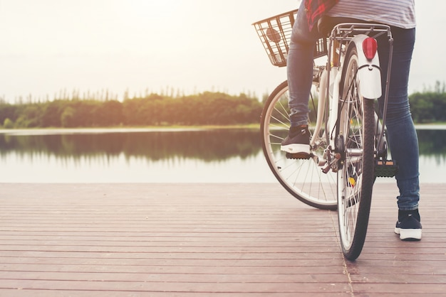 Close-up of young hipster woman holding her foot on bicycle peda Free Photo