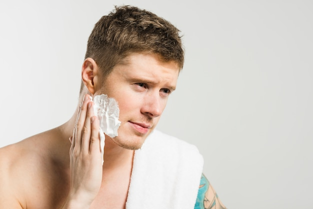 Close-up of a young man applying shaving foam on his cheek against grey background Free Photo