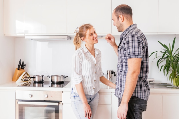 Close-up of a young man feeding graham cracker to his girlfriend in the kitchen Free Photo