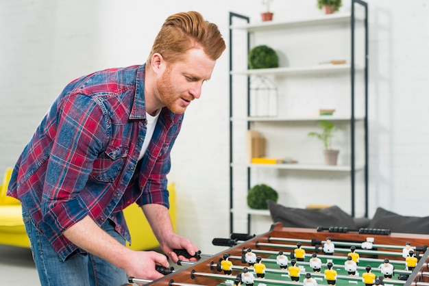 Close-up of young man playing the football table soccer game at home Free Photo