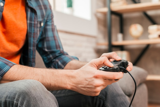 Close-up of a young man playing game console at home Free Photo