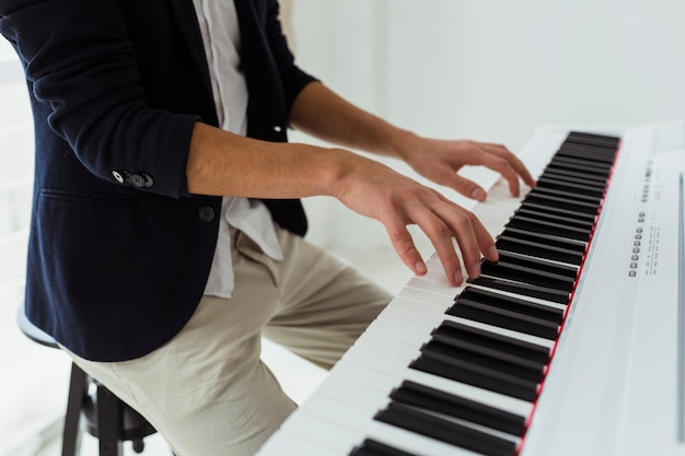 Close-up of young man's hand playing the piano Free Photo