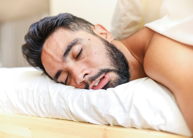 Close-up of a young man sleeping on bed Free Photo