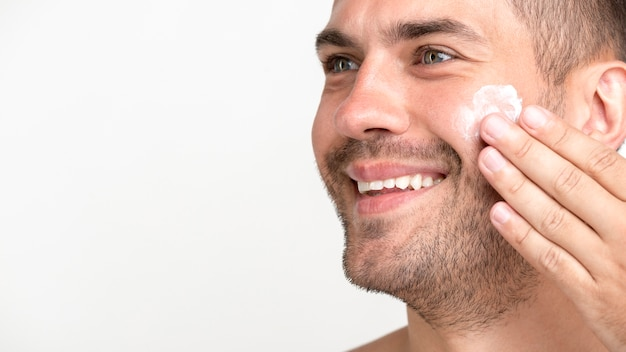 Close-up of young man smiling applying cream on face Free Photo