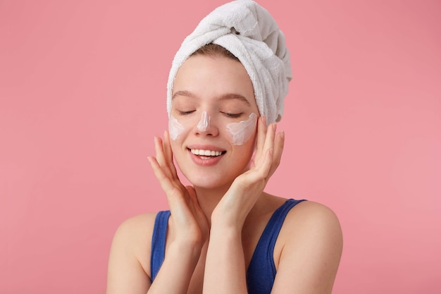 Close up of young nice glad woman with natural beauty with a towel on her head after shower, stands and puts on face cream with closed eyes. Free Photo