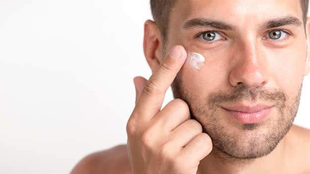 Close-up of young stubble man applying cream on her face Free Photo