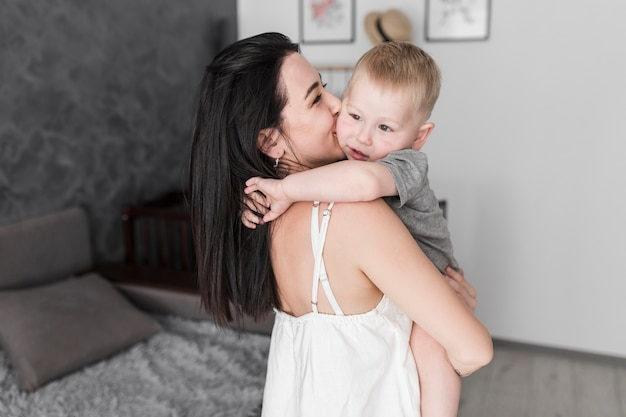 Close-up of young woman carrying her little cute son kissing on his cheeks Free Photo