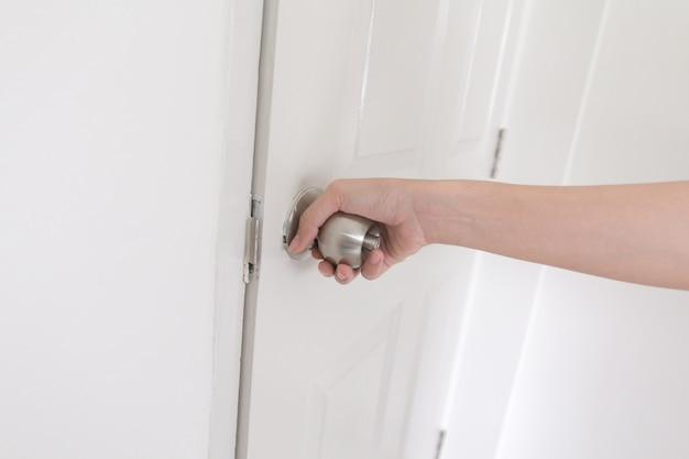 Close-up young woman handle stainless door knob Premium Photo