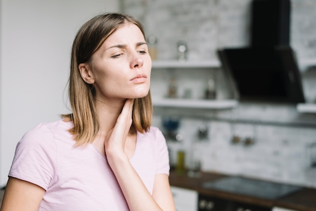 Close-up of a young woman having neck pain Free Photo