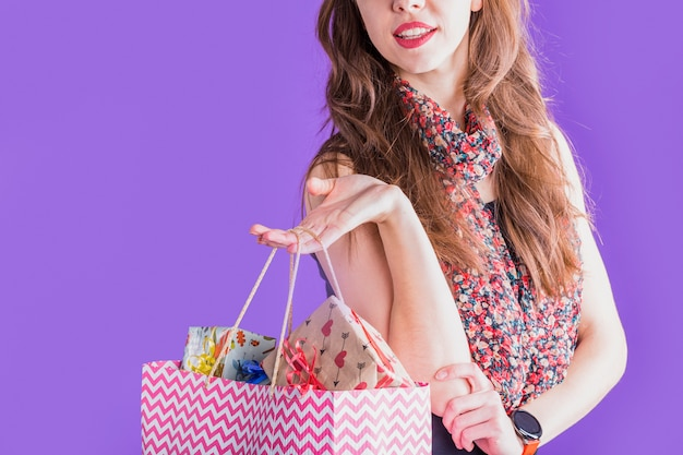 Close-up of young woman holding shopping paper bag with wrapped gift boxes Free Photo