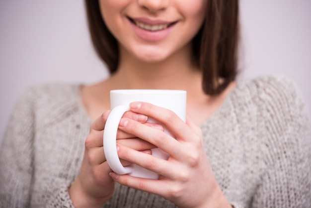 Close-up young woman is holding a cup of tea. Premium Photo