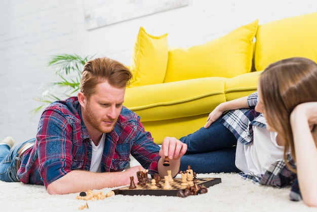 Close-up of young woman looking at man playing the chess game Free Photo