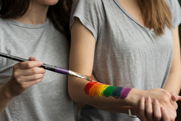 Close-up of a young woman painting the lbgt flag over her girlfriend's hand with paintbrush Free Photo