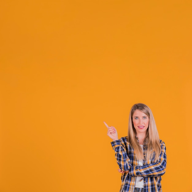 Close-up of a young woman pointing his finger upward against an orange backdrop Free Photo