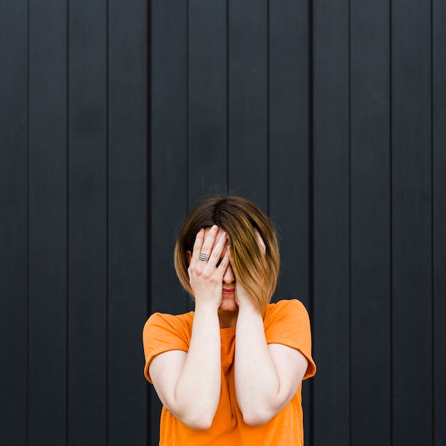 Close-up of a young woman standing against black wall covering her face with hands Free Photo